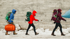 Three people walk on a snowy sidewalk carrying backpacks and luggage